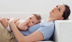 Trött mamma med bebis