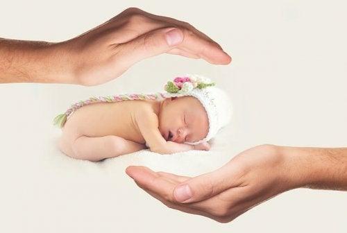 Barn som sover mellan händer