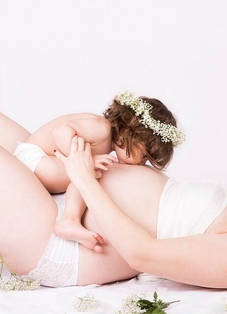Flicka som pussar mammas mage