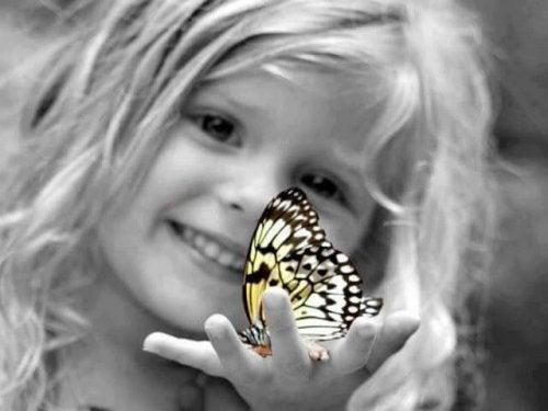 Flicka med fjäril i handen