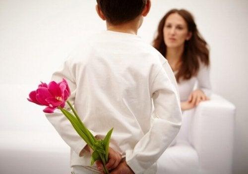 Pojke med blommor bakom rygg