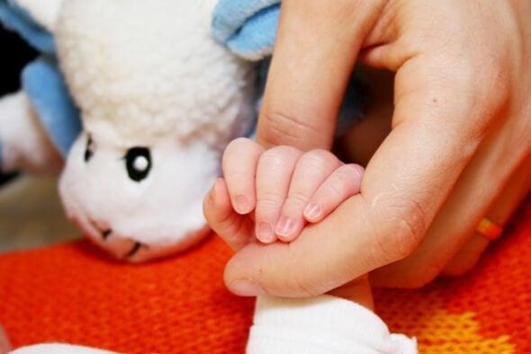 Mor som håller en liten hand