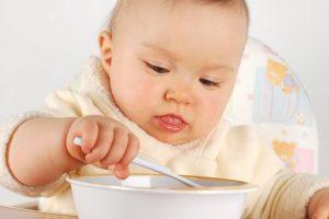 Bebis äter med sked