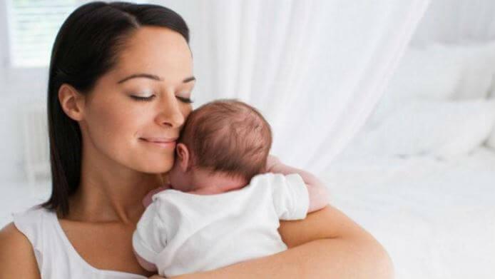 Mor som håller om bebis.