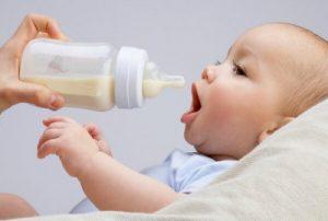 ett spädbarn som dricker från nappflaska
