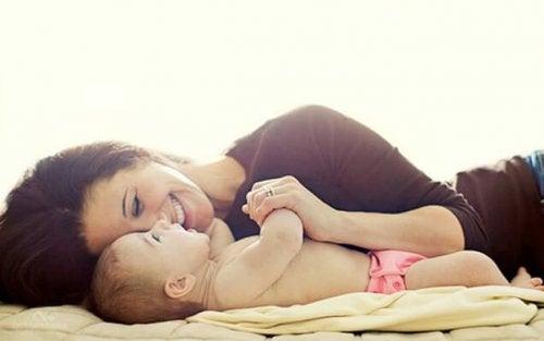 Mamma som ler bredvid sin bebis.
