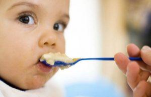 Bebis som matas med päronpuré