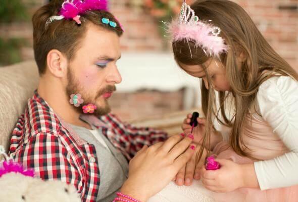En dotter målar naglarna på pappa
