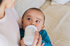 Bebis som matas med flaska