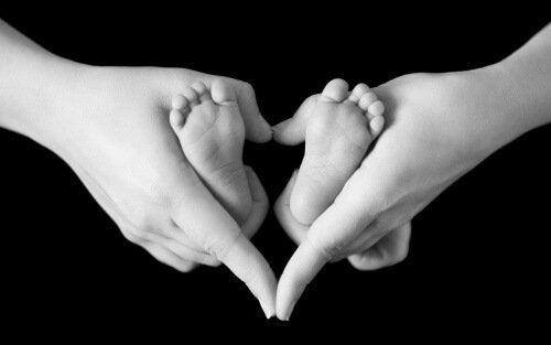 Händer som håller i en bebis fötter.