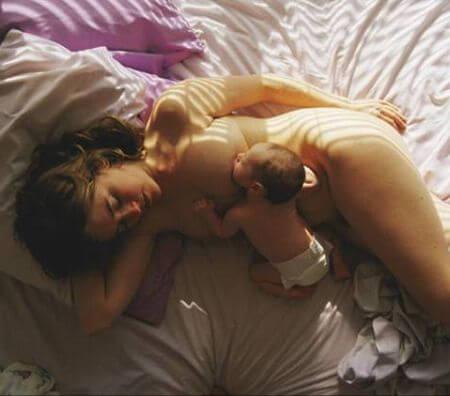 Mamma som ligger i sängen med bebis.