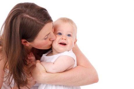 Mor som pussar bebis.