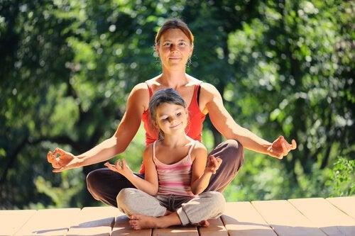 Mor och dotter som gör avslappningsövningar.