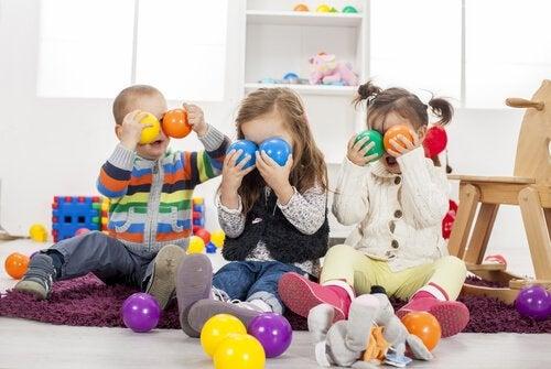 Barn som håller bollar framför ansiktet.