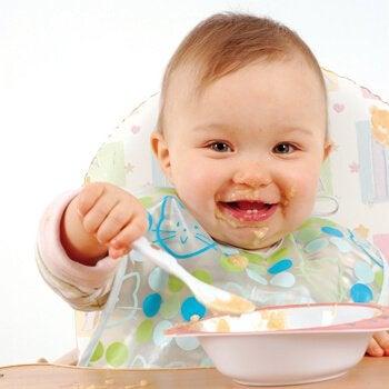 Bebis som äter och är glad.