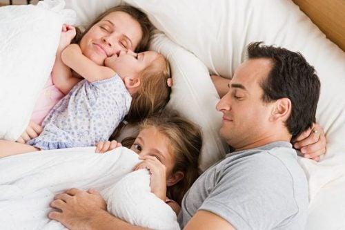 En familj som vilar tillsammans i sängen.