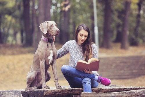 En tonåring med en hund läser en bok