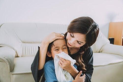 Mamma torkar slem och snor från sitt barns näsa