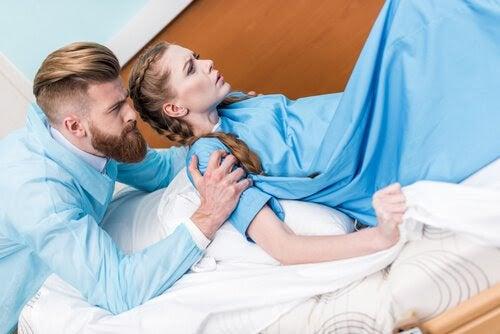 Man håller om axlarna på kvinna med ambulatorisk epiduralbedövning