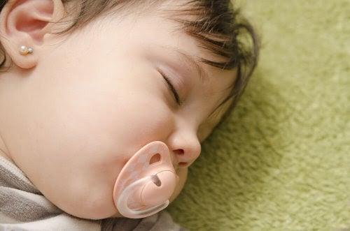 Bebis sover med napp i munnen
