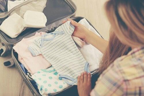 Kvinna packar babykläder i resväska
