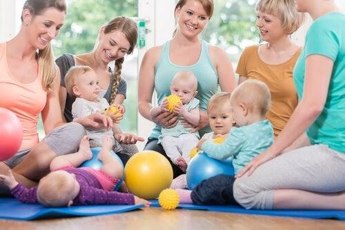 Mammor och bebisar på mattor med bollar