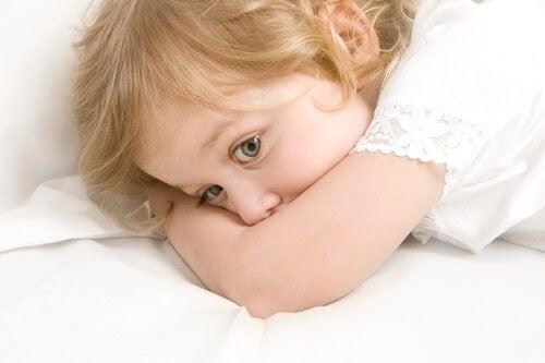 språkförsening: barn ligger på mage med armen framför munnen