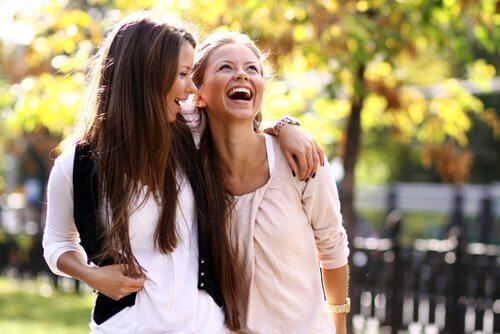 Två väninnor pratar och skrattar tillsammans.