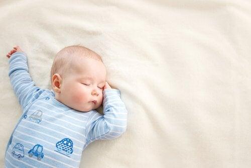 Bebis som sover i sängen.