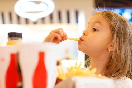 flicka äter snabbmat