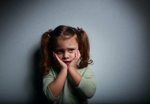 Flicka håller sig för ansiktet av oro