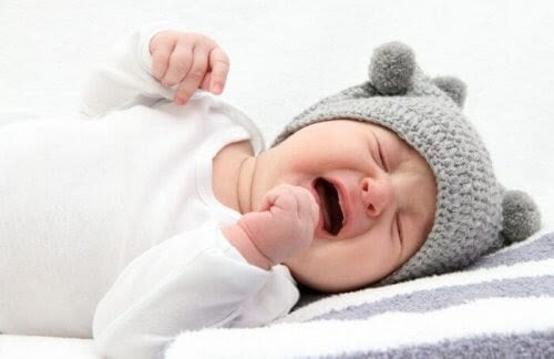 spädbarn som gråter, har grå mössa på sig