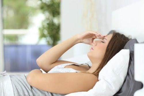 Kvinna i säng håller sig för pannan