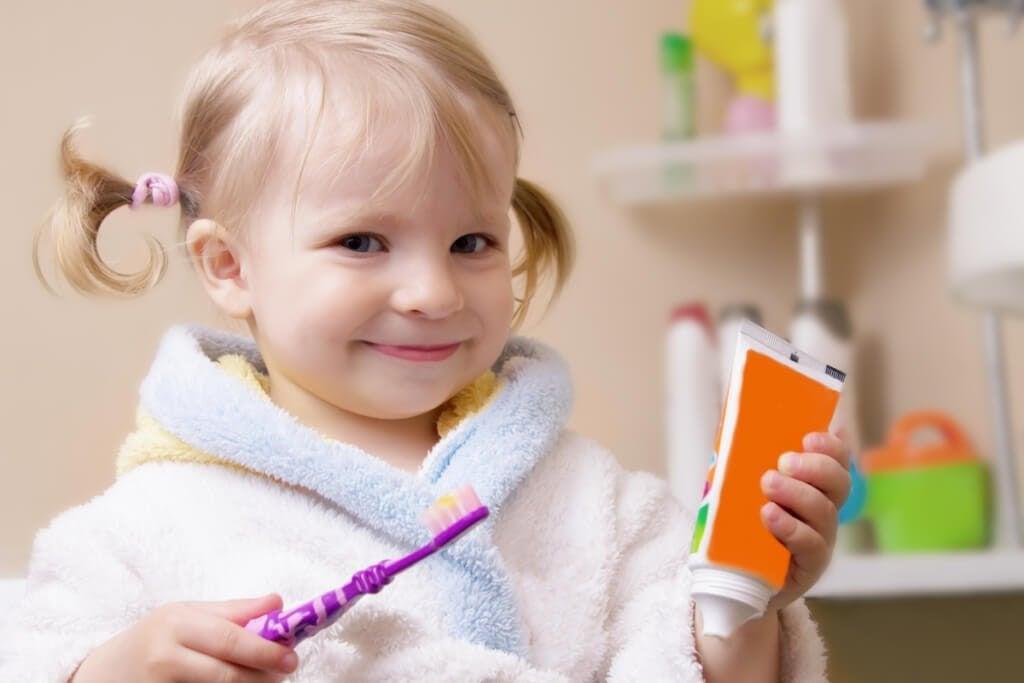 liten flicka med tandborste och tandkrämstub