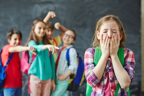 Tre barn pekar och skrattar åt ledsen flicka