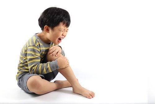 Vad är växtvärk hos barn och ungdomar? Pojke håller sig för knäet och gråter