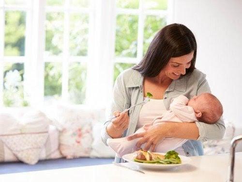 Mamma äter måltid med spädbarn i famnen