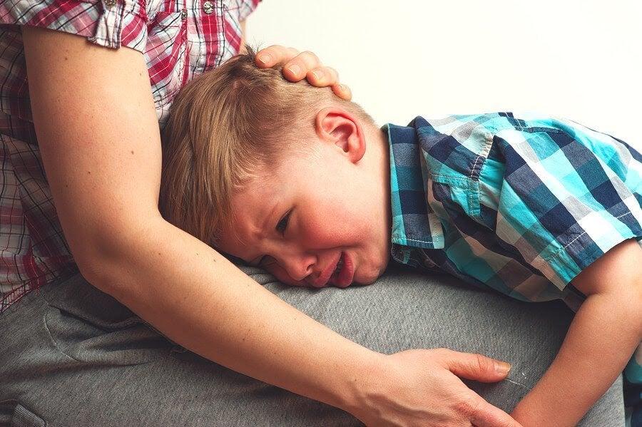 pojke gråter i sin mammas knä