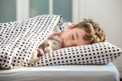 barn sover i säng med nalle