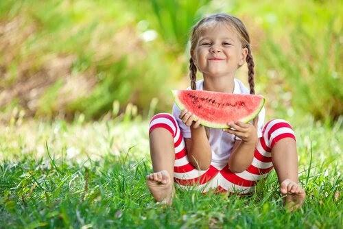 Glad flicka sitter i gräset och äter vattenmelon