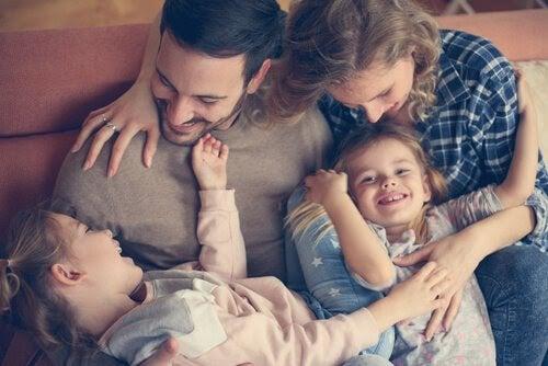 Mamma, pappa och två barn gosar