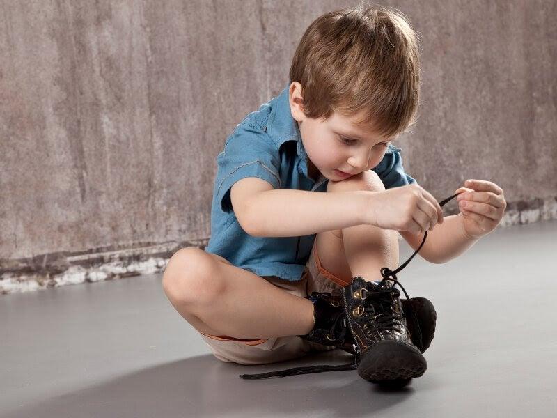 Pojke knyter skorna