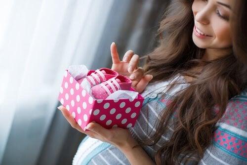 Gravid kvinna med paket med rosa bebisskor i