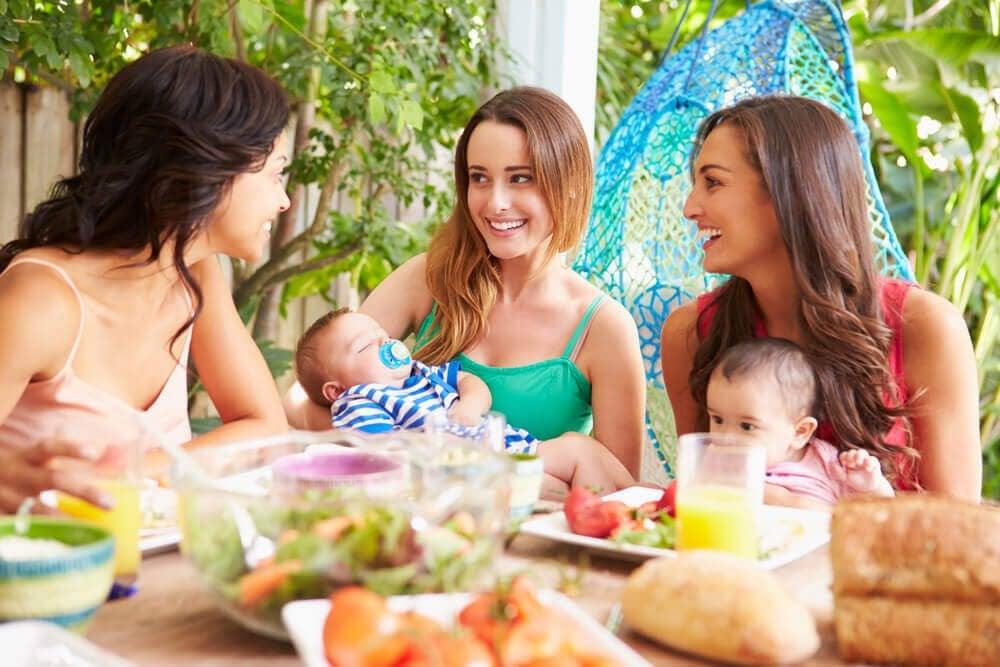 Tre kvinnor med bebisar sitter vid ett dukat bord