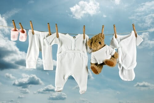 Barnkläder och en nalle hänger på tvättlina