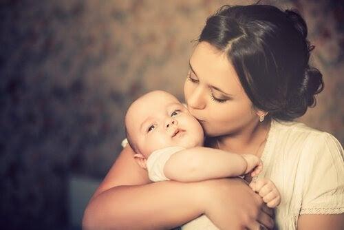 en mammas kärlek: mamma kysser spädbarn