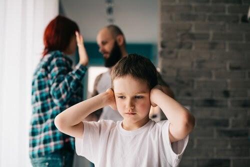 barn håller för öronen, föräldrar bråkar i bakgrunden