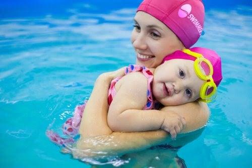 Mamma och bebis i pool med matchande rosa badmössor