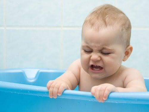 baby i badbalja, ser frustrerad ut