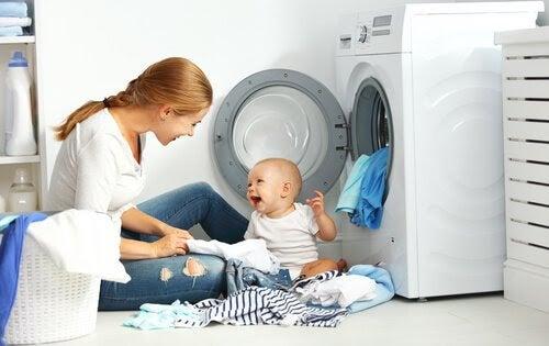 mamma och bebis sorterar tvätt vid tvättmaskin